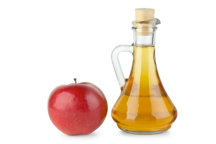 Decanter with apple vinegar and red apple